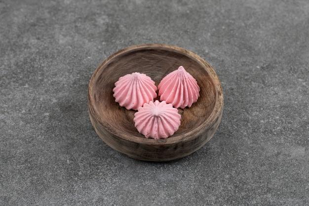 Bovenaanzicht van verse roze meringue koekjes in houten kom