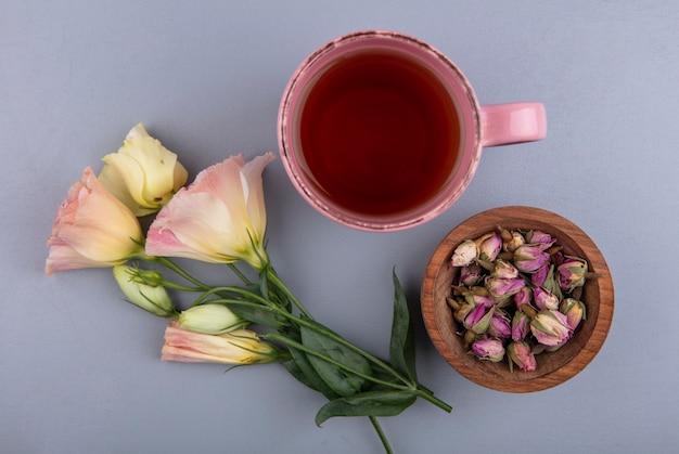 Bovenaanzicht van verse roze toppen op een houten kom met een kopje thee op een grijze achtergrond