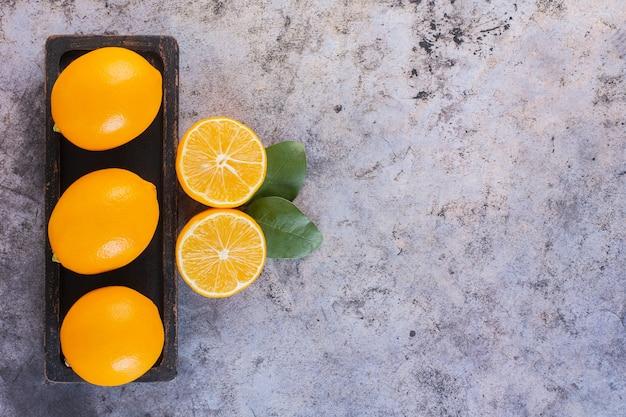 Bovenaanzicht van verse, sappige citroenen in een rij op houten plaat.