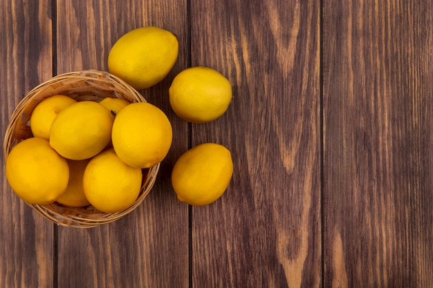 Bovenaanzicht van verse, sappige citroenen op een emmer met citroenen geïsoleerd op een houten oppervlak met kopie ruimte