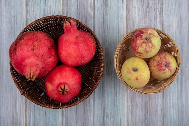 Bovenaanzicht van verse, sappige en rossige granaatappels op een emmer met appels op een emmer op een grijze achtergrond