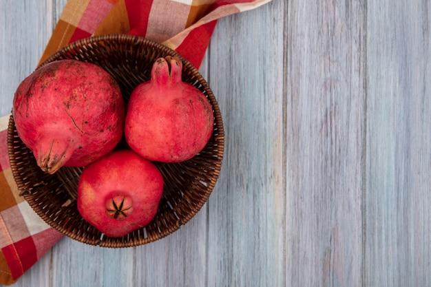 Bovenaanzicht van verse, sappige en rossige granaatappels op een emmer op een gecontroleerde doek op een grijze achtergrond met kopie ruimte