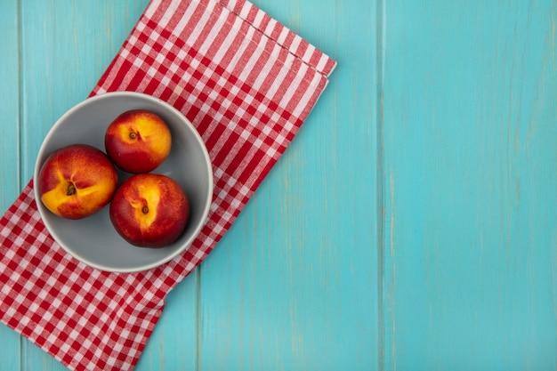 Bovenaanzicht van verse, sappige perziken op een kom op een rood geruite doek op een blauwe houten muur met kopie ruimte