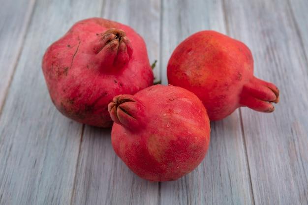 Bovenaanzicht van verse, sappige rode granaatappels geïsoleerd op een grijze achtergrond