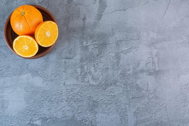 Bovenaanzicht van verse, sappige sinaasappelen in houten kom over grijs.