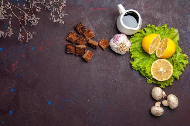 Bovenaanzicht van verse schijfjes citroen met groene salade op donker