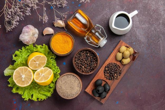Bovenaanzicht van verse schijfjes citroen met olijven en kruiden op dark