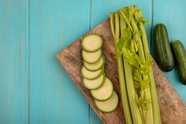Bovenaanzicht van verse selderij met gehakte courgettes op een houten keukenbord met komkommers geïsoleerd op een blauwe houten muur met kopie ruimte