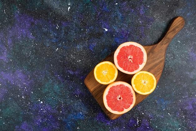 Bovenaanzicht van verse sinaasappel- en grapefruitschijfjes op een houten bord.