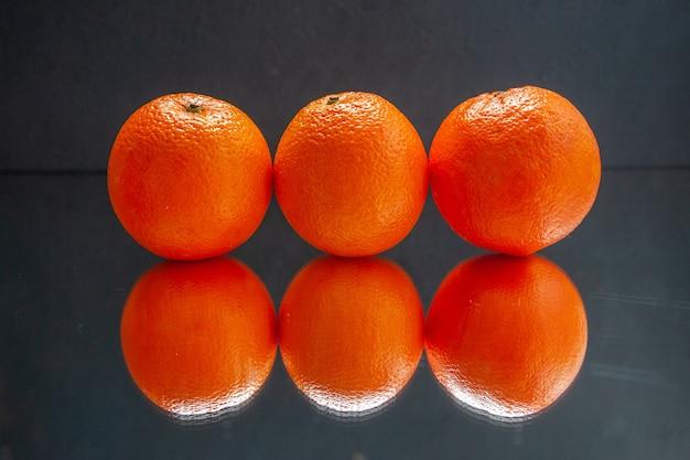 Bovenaanzicht van verse sinaasappelen die naast elkaar staan op een zwarte achtergrond met vrije ruimte