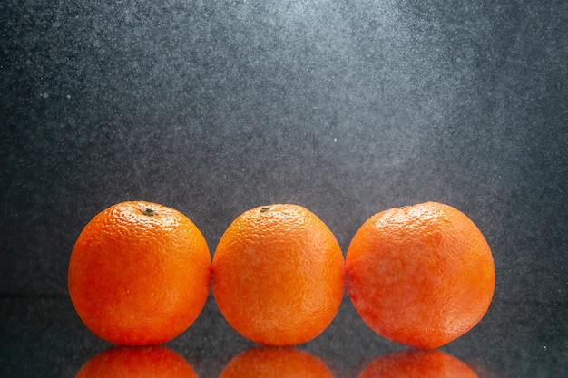 Bovenaanzicht van verse sinaasappelen die naast elkaar staan op licht op zwarte achtergrond met vrije ruimte
