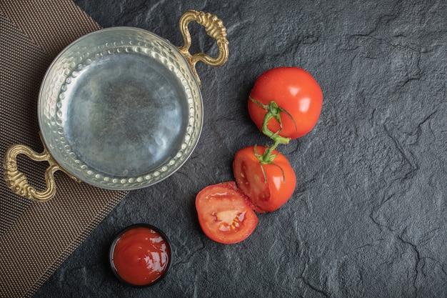Bovenaanzicht van verse tomaten geheel of half gesneden met ketchup naast pan.