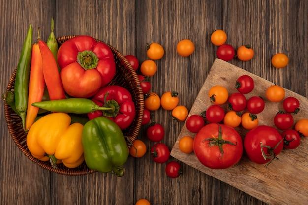 Bovenaanzicht van verse tomaten geïsoleerd op een houten keukenbord met kleurrijke paprika's op een emmer op een houten muur