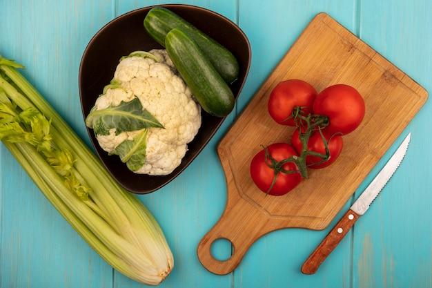 Bovenaanzicht van verse tomaten geïsoleerd op een houten keukenbord met mes met hele komkommers en bloemkool op een emmer met selderij geïsoleerd op een blauwe houten muur