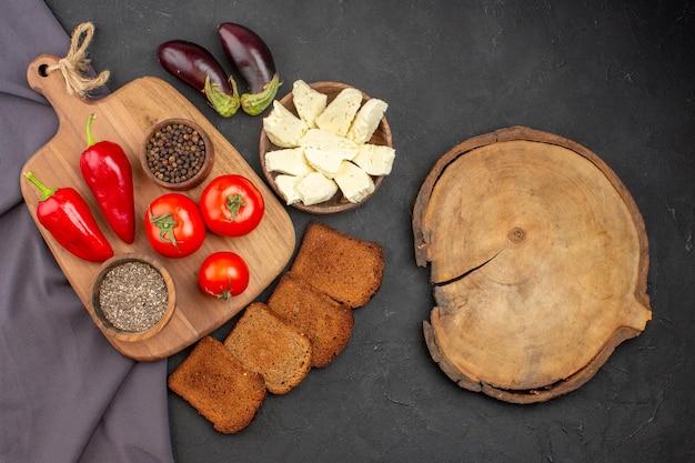 Bovenaanzicht van verse tomaten met donker. brood broden en witte kaas op zwart