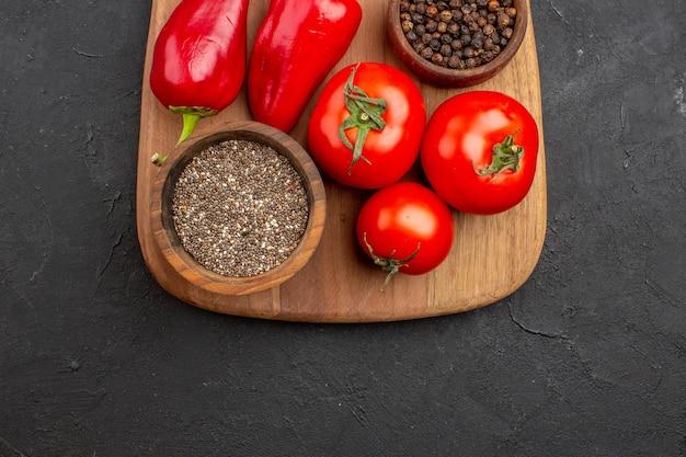 Bovenaanzicht van verse tomaten met kruiden en rode peper op zwart