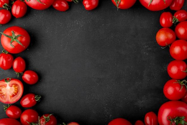 Bovenaanzicht van verse tomaten op zwarte achtergrond met kopie ruimte