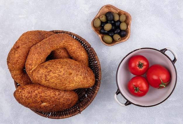 Bovenaanzicht van verse turkse bagels op een emmer met pasteitjes met olijven op een houten kom op een witte achtergrond
