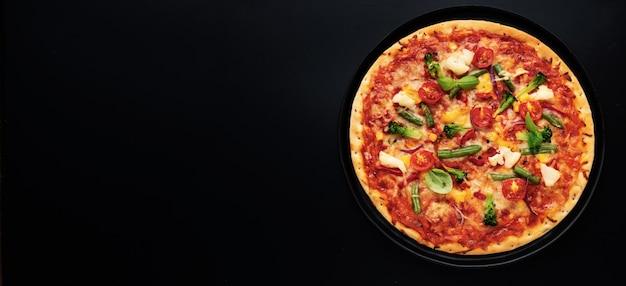 Bovenaanzicht van verse vegetarische pizza met tomaten, kaas en groenten