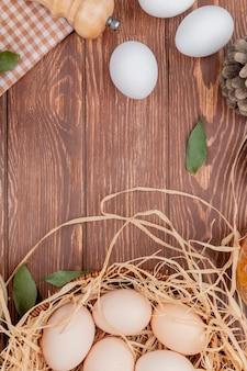 Bovenaanzicht van verse witte en crème gekleurde kippeneieren met dennenappels op een houten achtergrond met kopie ruimte