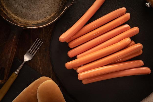 Bovenaanzicht van verse worstjes voor hotdogs op donker met broodjes.