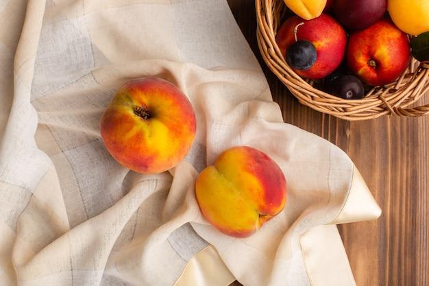 Bovenaanzicht van verse zachte perziken samen met fruit in een mand