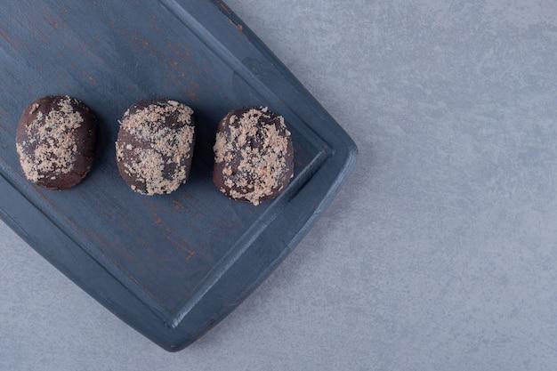 Bovenaanzicht van verse zelfgemaakte chocoladekoekjes op een houten bord