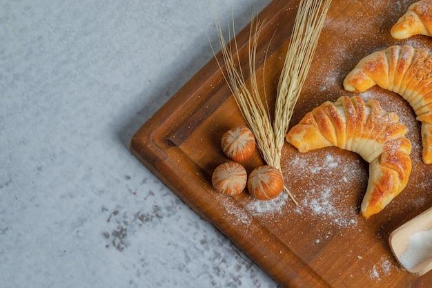 Bovenaanzicht van verse zelfgemaakte croissants op een houten bord over grijze ondergrond.