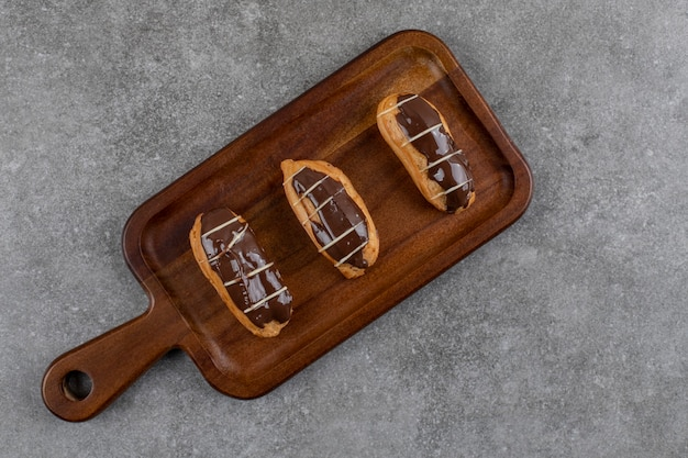 Bovenaanzicht van verse zelfgemaakte donuts op een houten bord.