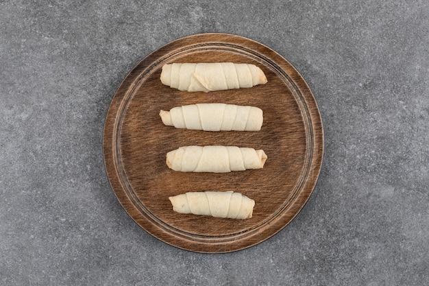 Bovenaanzicht van verse zelfgemaakte gerolde koekjes op een houten bord.