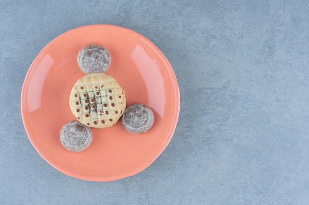 Bovenaanzicht van verse zelfgemaakte koekjes. heerlijke snacks op oranje plaat.