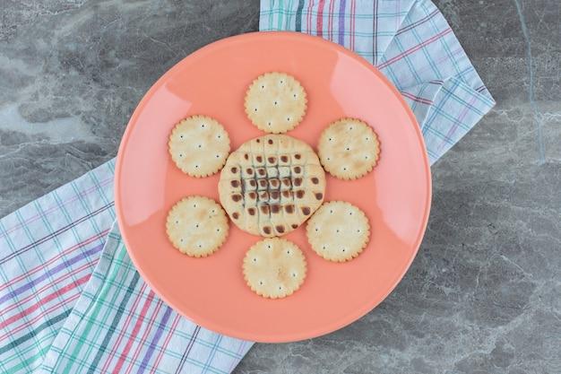 Bovenaanzicht van verse zelfgemaakte koekjes op oranje bord.