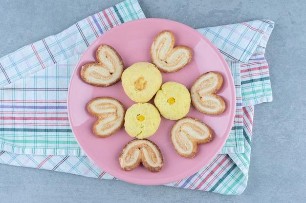 Bovenaanzicht van verse zelfgemaakte koekjes op roze plaat.