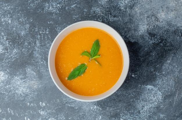Bovenaanzicht van verse zelfgemaakte tomatensoep in witte kom over grijze tafel.