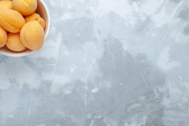 Bovenaanzicht van verse zoete abrikozen zacht en lekker fruit binnen plaat op licht bureau, fruit vers voedsel maaltijd vitamine