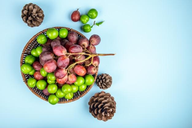 Bovenaanzicht van verse zoete druif met groene zure pruimen in een rieten mand en kegels op blauwe tafel met kopie ruimte