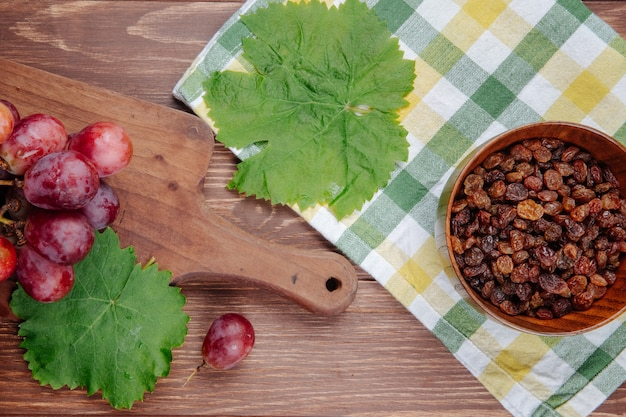 Bovenaanzicht van verse zoete druif op een houten snijplank, groene druivenbladeren en rozijnen in een kom op geruite stof op houten tafel