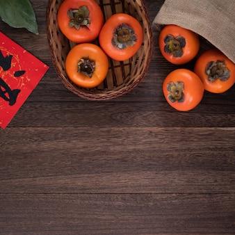 Bovenaanzicht van verse zoete kaki op houten tafel achtergrond voor chinees nieuwjaar ontwerp