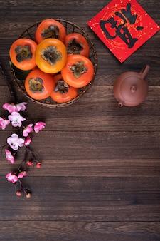 Bovenaanzicht van verse zoete kaki op houten tafel achtergrond voor chinees nieuwjaar