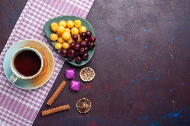 Bovenaanzicht van verse zoete kersen in plaat met kopje thee op het donkere oppervlak