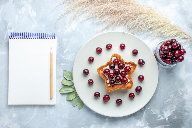 Bovenaanzicht van verse zure kersen in plaat met stervormige romige cake kladblok op wit wit, fruit zure zomer cake koekje