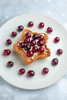 Bovenaanzicht van verse zure kersen in plaat met stervormige romige cake op licht, fruit zure bes vitamine zomer
