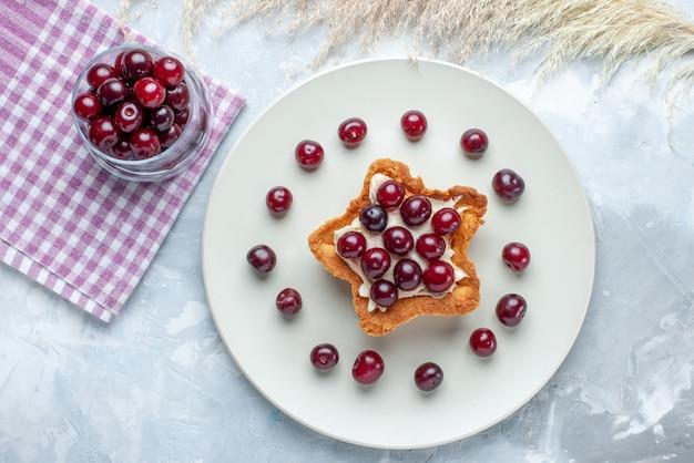 Bovenaanzicht van verse zure kersen in plaat met stervormige romige cake op licht-witte vloer fruit zure bes zomer