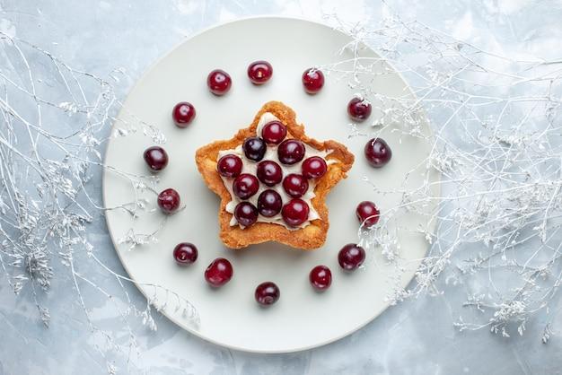 Bovenaanzicht van verse zure kersen in plaat met stervormige romige cake op lichtwit, fruitzure bes vitamine zomer bakroom