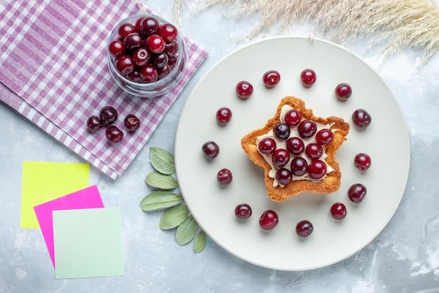 Bovenaanzicht van verse zure kersen in plaat met stervormige romige cake op wit wit bureau, fruit zure zomercake koekje