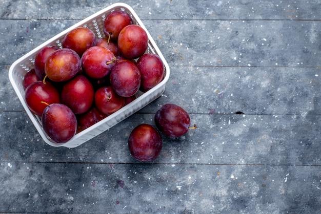 Bovenaanzicht van verse zure pruimen in witte mand op grijs, vers zuur mellow fruit