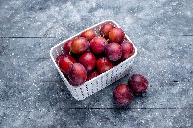 Bovenaanzicht van verse zure pruimen in witte mand op grijze vloer fruit vers zuur mellow rijp