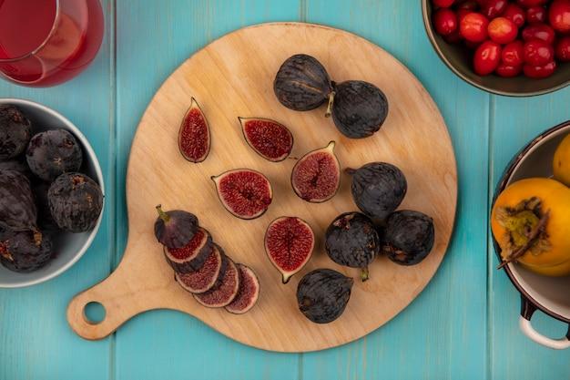 Bovenaanzicht van verse zwarte missie vijgen op een houten keukenbord met kaki fruit op een kom op een blauwe houten muur