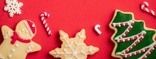 Bovenaanzicht van versierde peperkoek kerstkoekjes op rode tabelachtergrond met kopieerruimte, concept van vakantieviering.