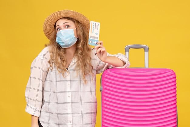 Bovenaanzicht van verwarde jonge dame die masker draagt met kaartje en in de buurt van haar roze tas staat